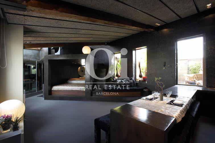 Vista de salón comedor con cocina americana de ático de diseño en venta en Nou de la Rambla