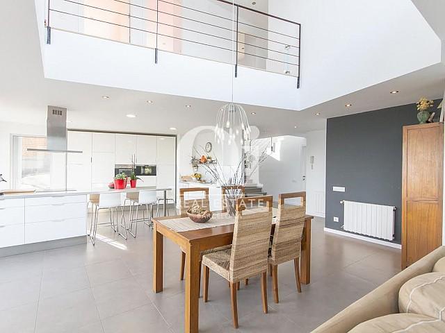 Vista de salón comedor con cocina americana en propiedad de lujo en venta en Sant Andreu de Llavaneres