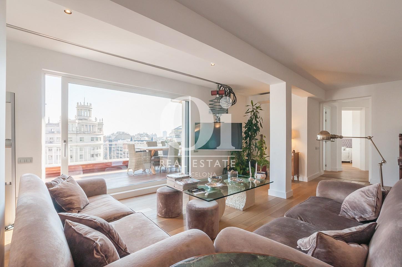 гостиная с большим панорамным окном и видом на город эксклюзивного пентхауса на продажу в Эйшампле