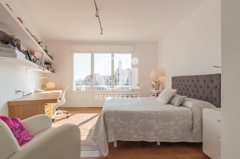 одна из четырех спален с большим окном эксклюзивного пентхауса на продажу в Эйшампле