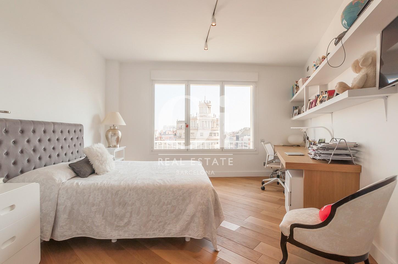 одна из спален с дизайнерской мебелью и большим окном эксклюзивного пентхауса на продажу в Эйшампле