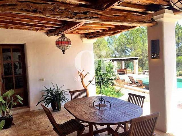 столовая зона, а также вид на бассейн и крытую веранду с зоной барбекю дома в аренду в районе Сан-Рафаэль, Ибица