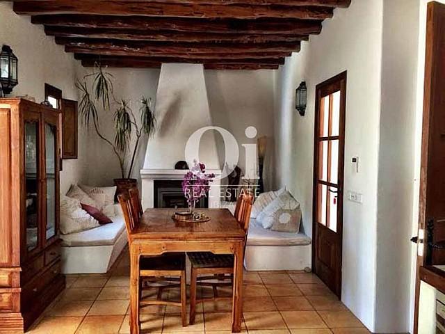 гостиная с камином и деревянными потолочными перекрытиями дома в аренду в районе Сан-Рафаэль, Ибица