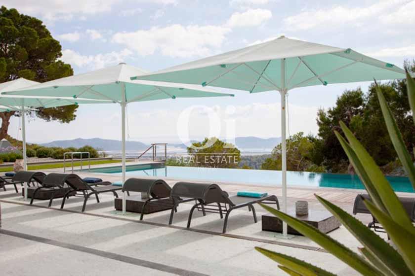 зона для отдыха у бассейна пож открытым небом, с солнечными зонтиками, красивым ландшафтным дизайном и видом на горы