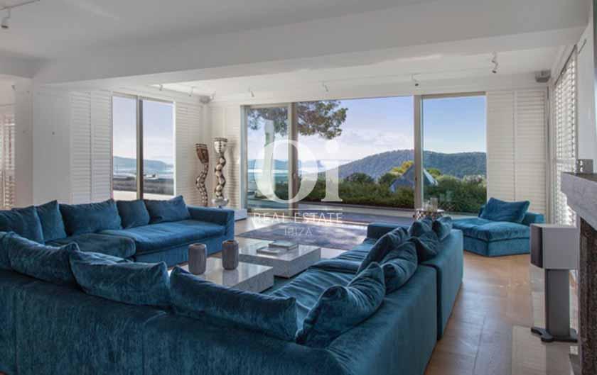 внутренний интерьер роскошной виллы на Ибице, солнечный зал с большим диваном и панорамными окнами