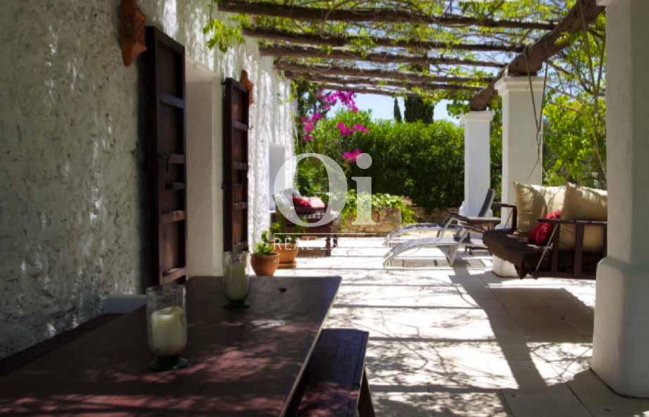 Крытая терраса и пышная растительность во дворе виллы на Ибице в арунду
