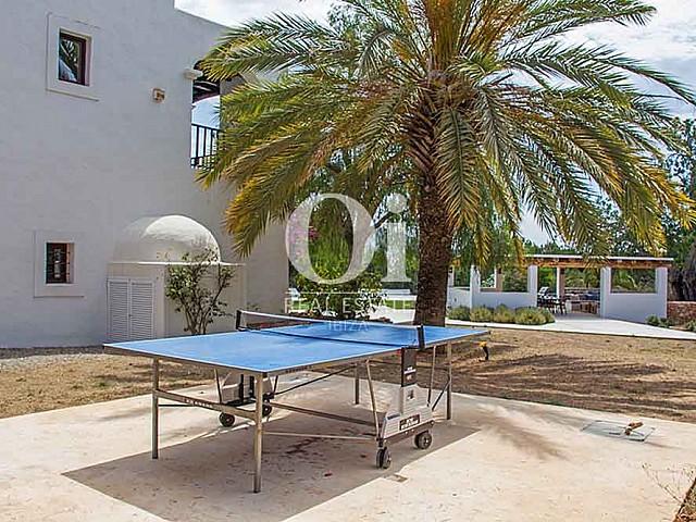 Уютный двор старинной виллы на острове Ибица, белокаменный фасад, пальмы и стол для игры в пинпонг