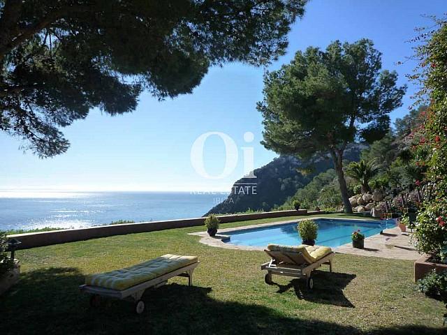 Вид с открытой терассы на большой бассейн и пышную растительность на вилле в аренду для отпуска на острове Ибица