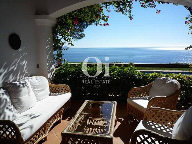 Вид на морское побережье с виллы в аренду на Ибице. открытая терраса с диваном и пышной растительностью