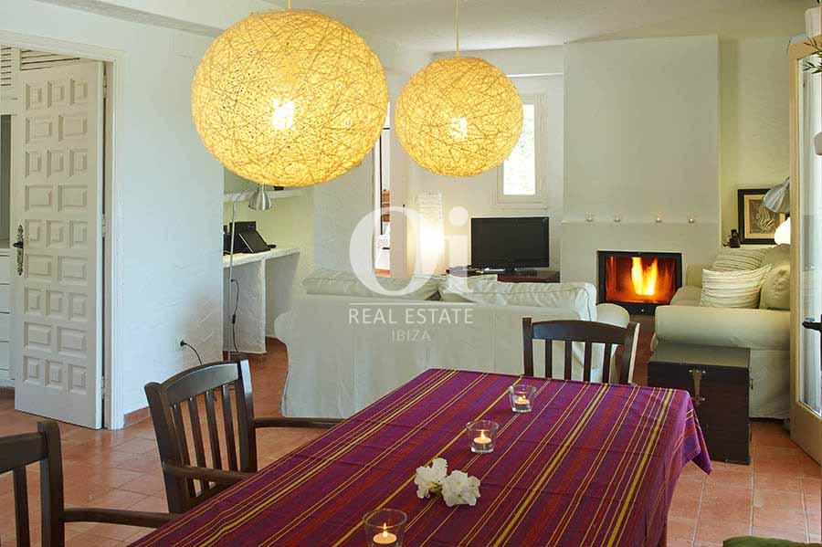 Salón comedor con chimenea de casa en alquiler de estancia en Ses Salinas, Ibiza
