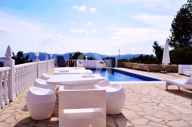 Exterior de la vila amb un espai de relax i la piscina amb hamaques