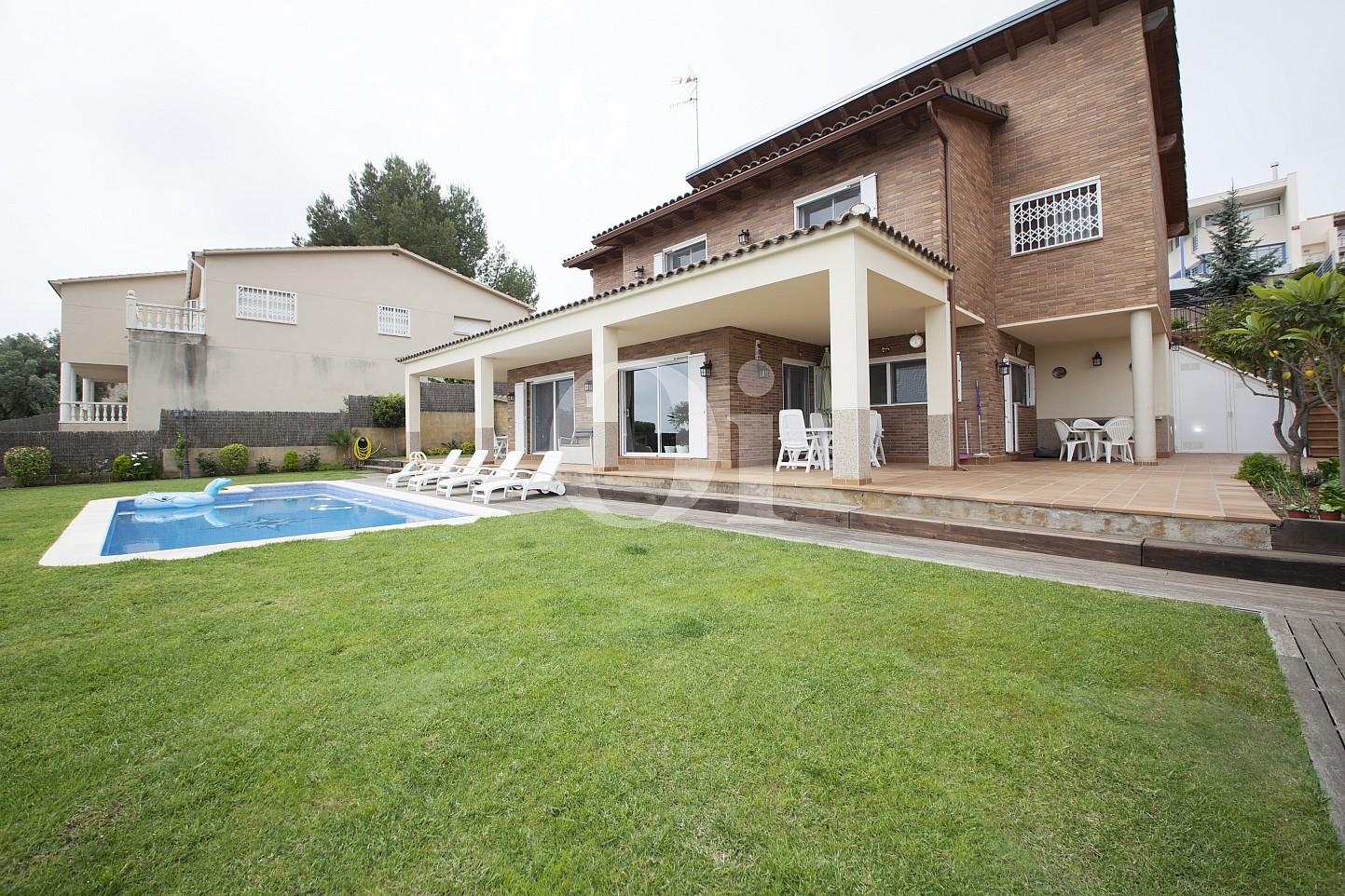 Exteriors de la casa amb el jardí i la piscina