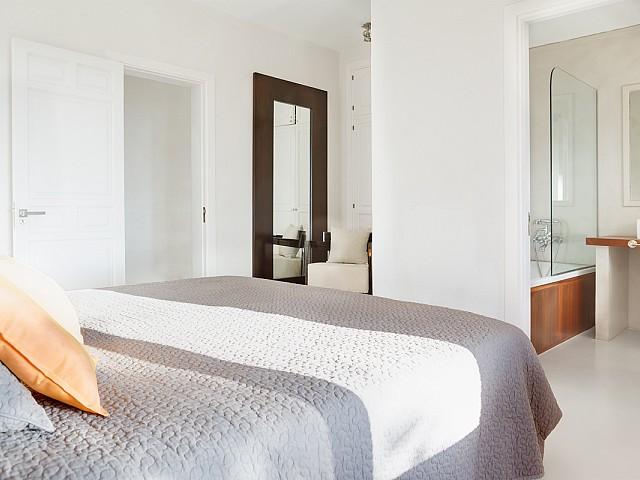 Уютная спальня с большими окнами и потрясающими видами на шикарной вилле в краткосрочную аренду на Ибице