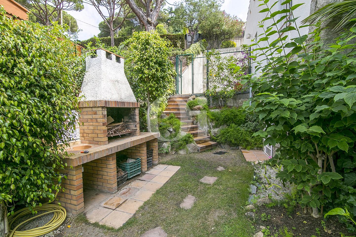 Espectacular patio trasero con jardín y barbacoa en sensacional casa en venta ubicada en Cabrils
