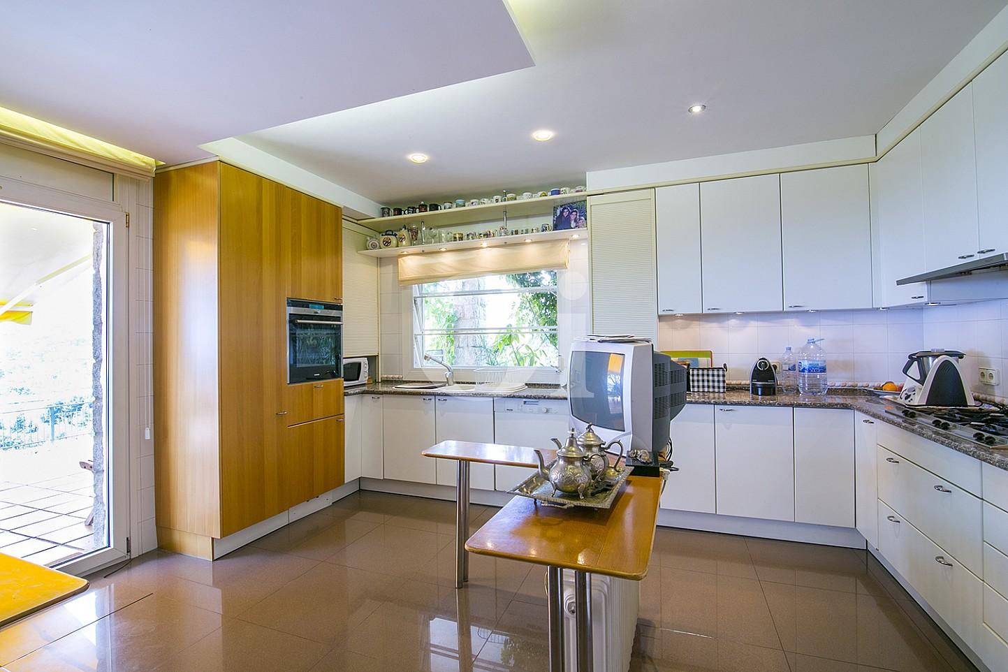 Luminosa cocina equipada y de estilo americana abierta a la zona exterior de la vivienda situada en Cabrils
