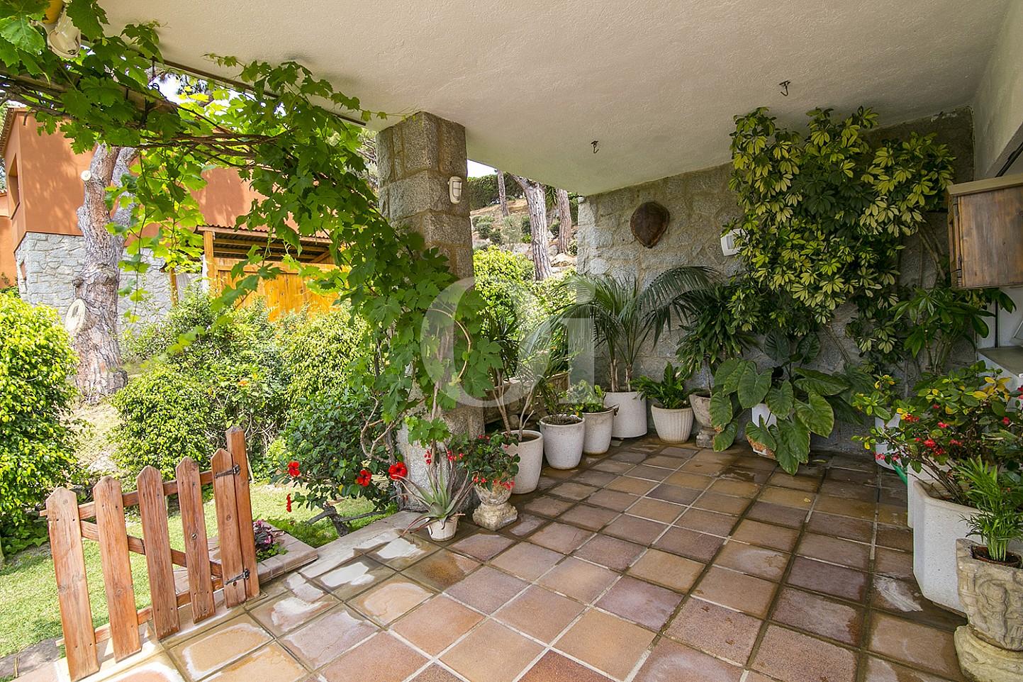 Luminosa terraza exterior rodeada de espectaculares plantas que dan un ambiento más calido en espectacular casa en venta en Cabrils