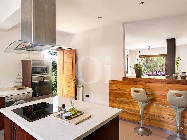 Lujosa cocina equipada y de estilo americano con vistas al exterior en excepcional casa en venta en Ibiza