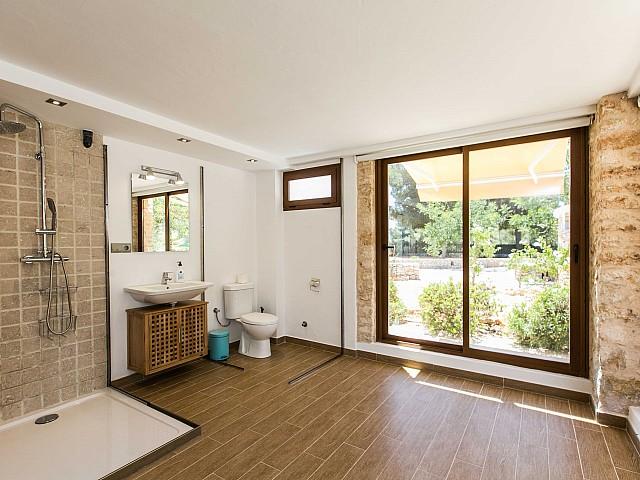 Luminoso baño completo con plato de ducha, aseo y vistas exteriores en espectacular casa en alquiler situada en Ibiza