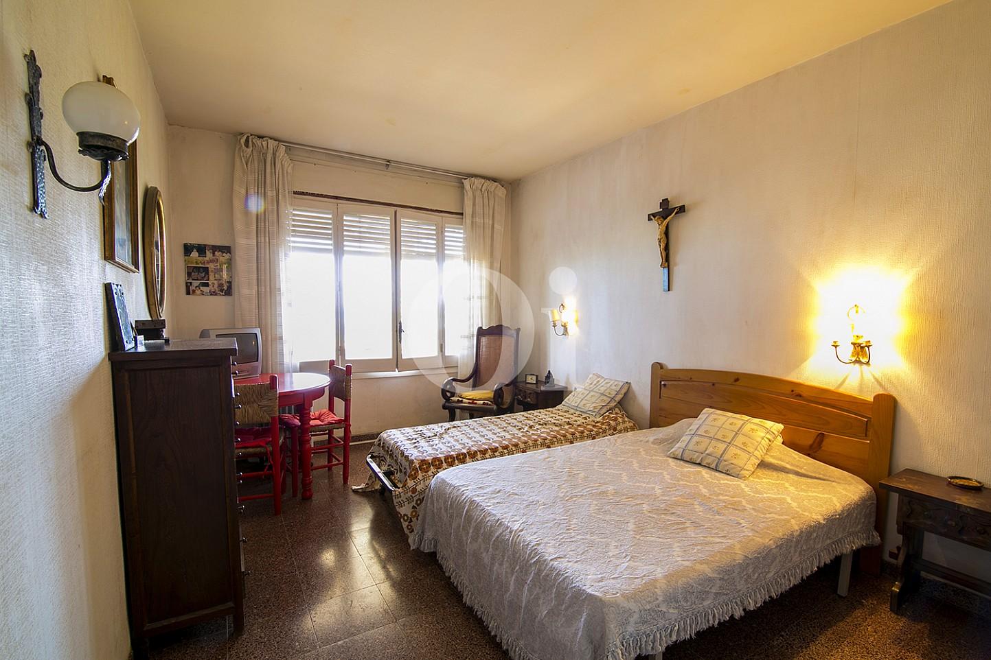 vistes de lluminosa habitació doble amb llit de matrimoni i vistes exteriors en pis en venda situat a Caldetes