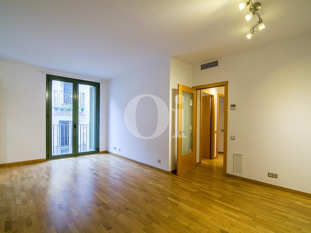 vista de salón comedor con balcón y suelos de parquet en piso en venta en el centro de Barcelona