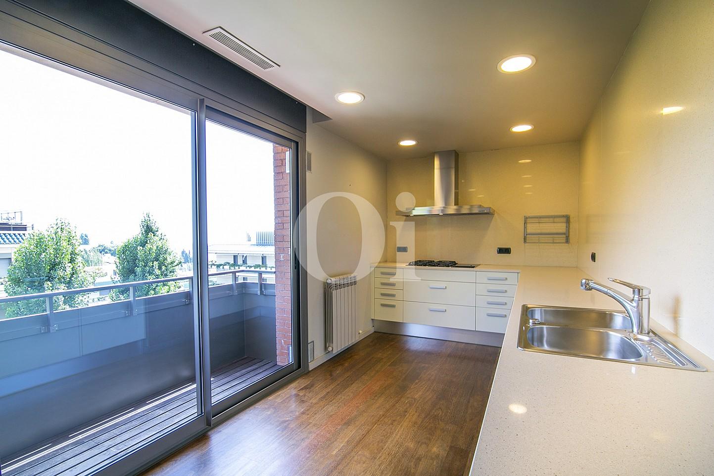 vista de cocina de diseño con salida a balcon en casa de lujo en venta en barcelona