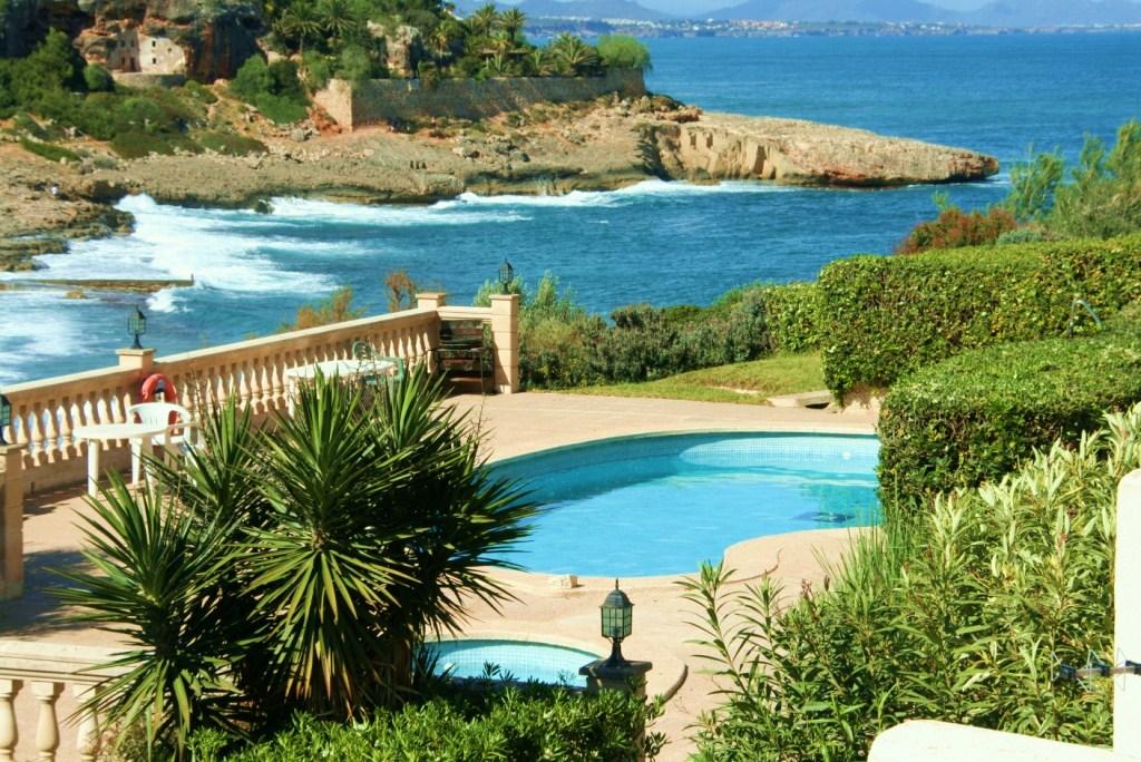Vistes a la piscina i al mar d'una adossada en venda  a Cala Murada, Mallorca