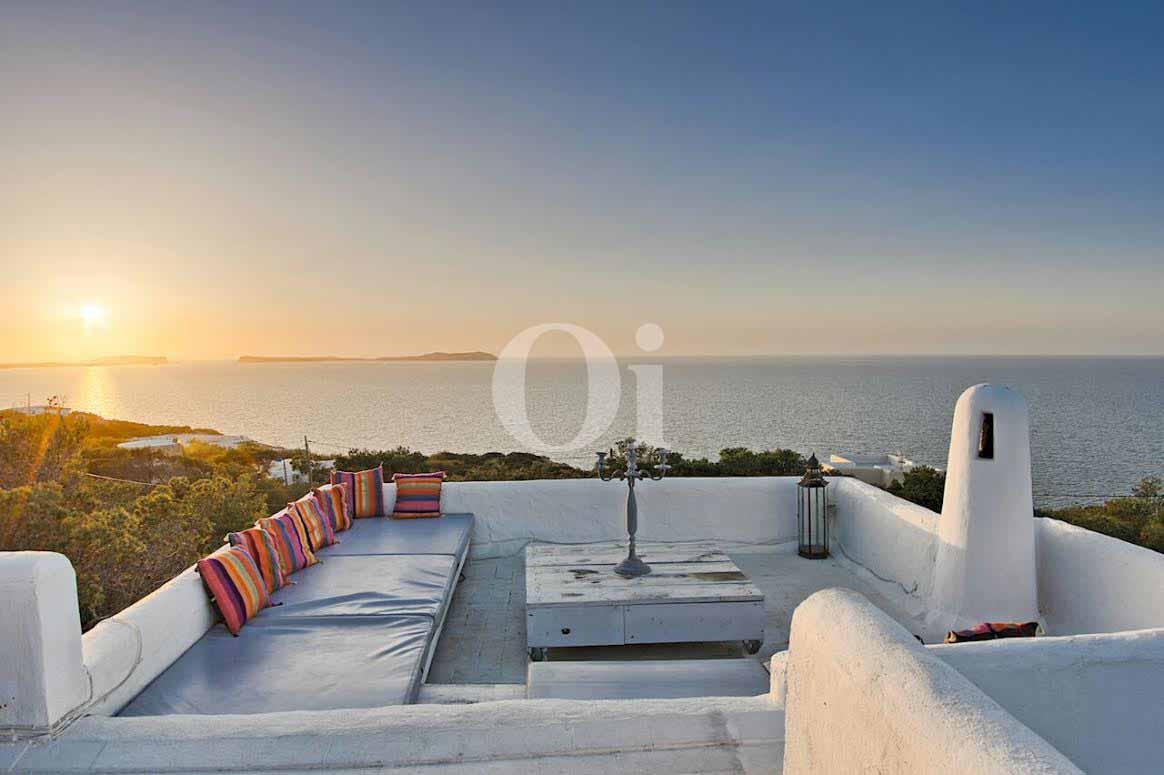 vista de zona de relax con vistas al mar y al atardecer en villa ibicenca en venta