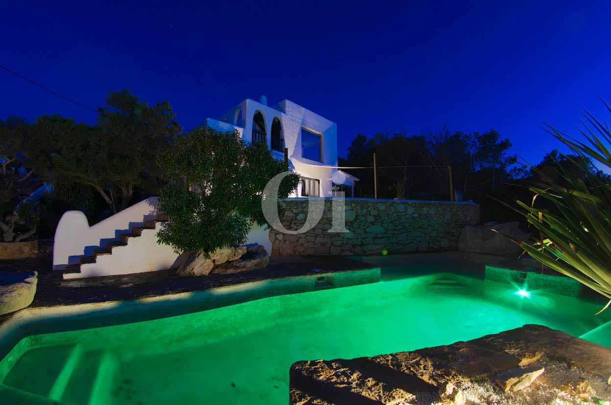 vista de piscina iluminada con leds de colores en villa estilo ibicenco en venta