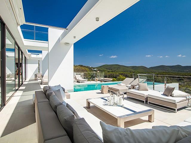 Zona de relax exterior i piscina d'una impressionant vila de luxe en lloguer a Es Cubells, Eivissa