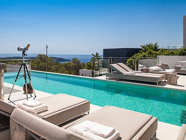 Piscina con hamacas de una impresionante villa de lujo en alquiler en Es Cubells, Ibiza