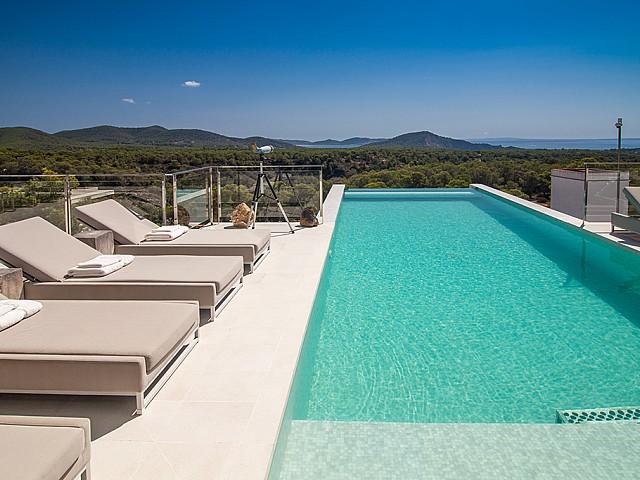 Piscina amb hamaques d'una impressionant vila de luxe en lloguer a Es Cubells, Eivissa