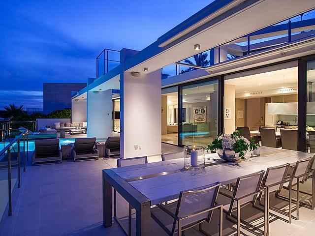 Exteriors amb menjador i piscina d'una impressionant vila de luxe en lloguer a Es Cubells, Eivissa