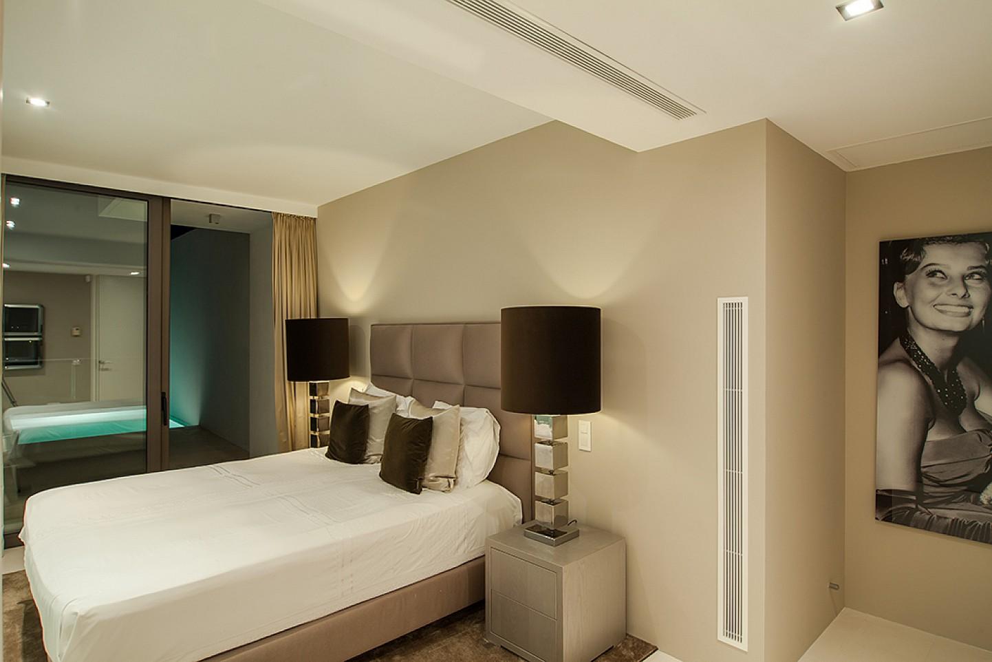 Dormitori amb sortida a la piscina d'una impressionant vila de luxe en lloguer a Es Cubells, Eivissa