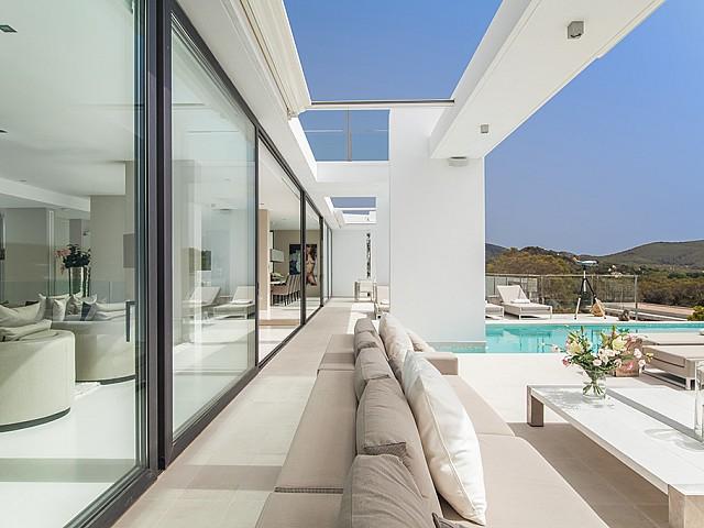 Zona de relax exterior y piscina de una impresionante villa de lujo en alquiler en Es Cubells, Ibiza