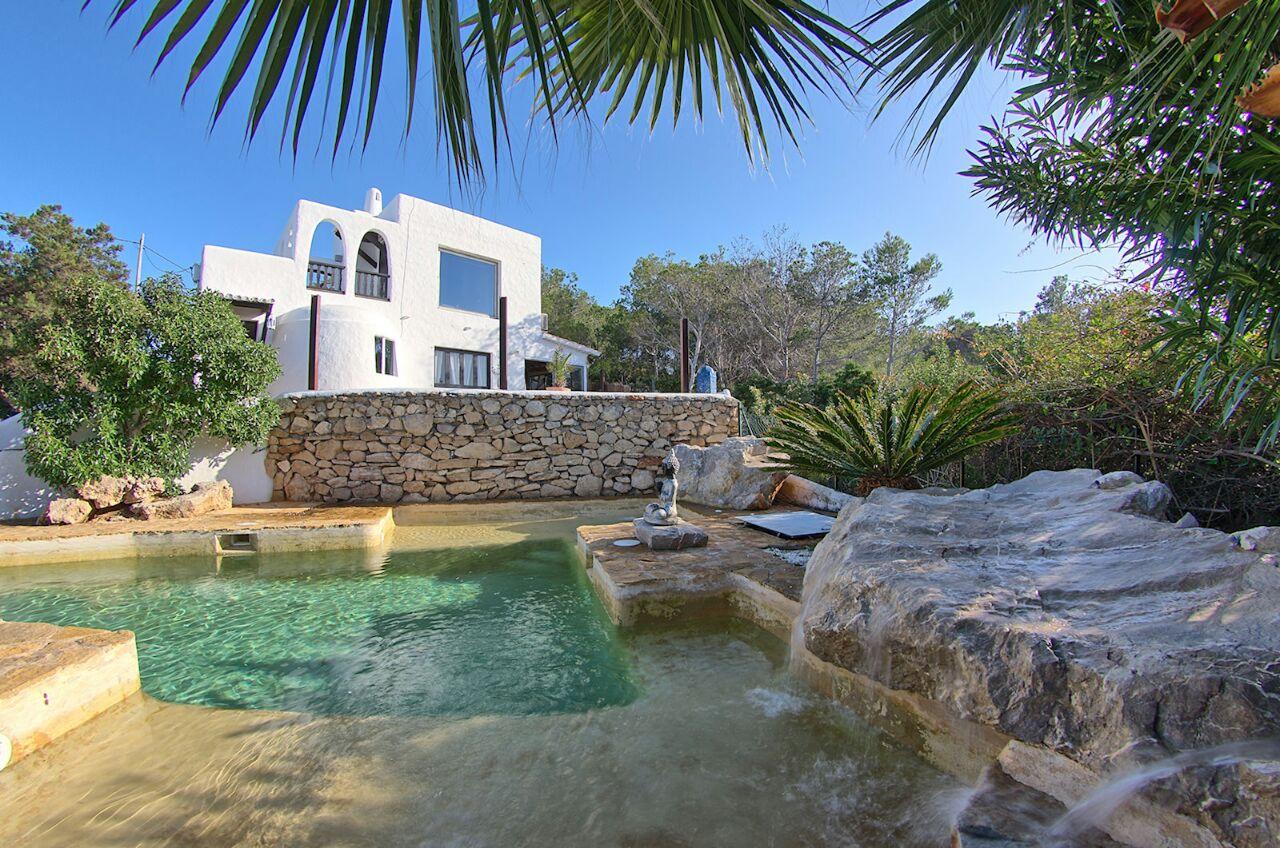 Vistas exteriores de la villa con la piscina natural