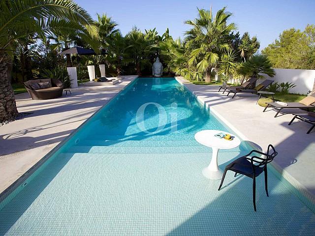 Gran piscina exterior amb hamaques