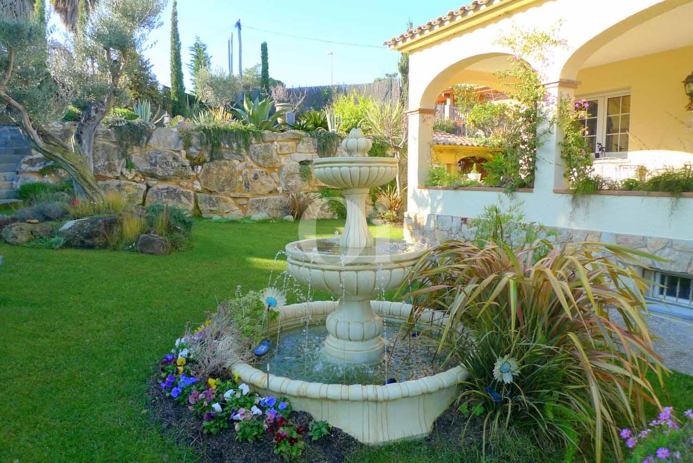 Jardín precioso con una fuente en el centro