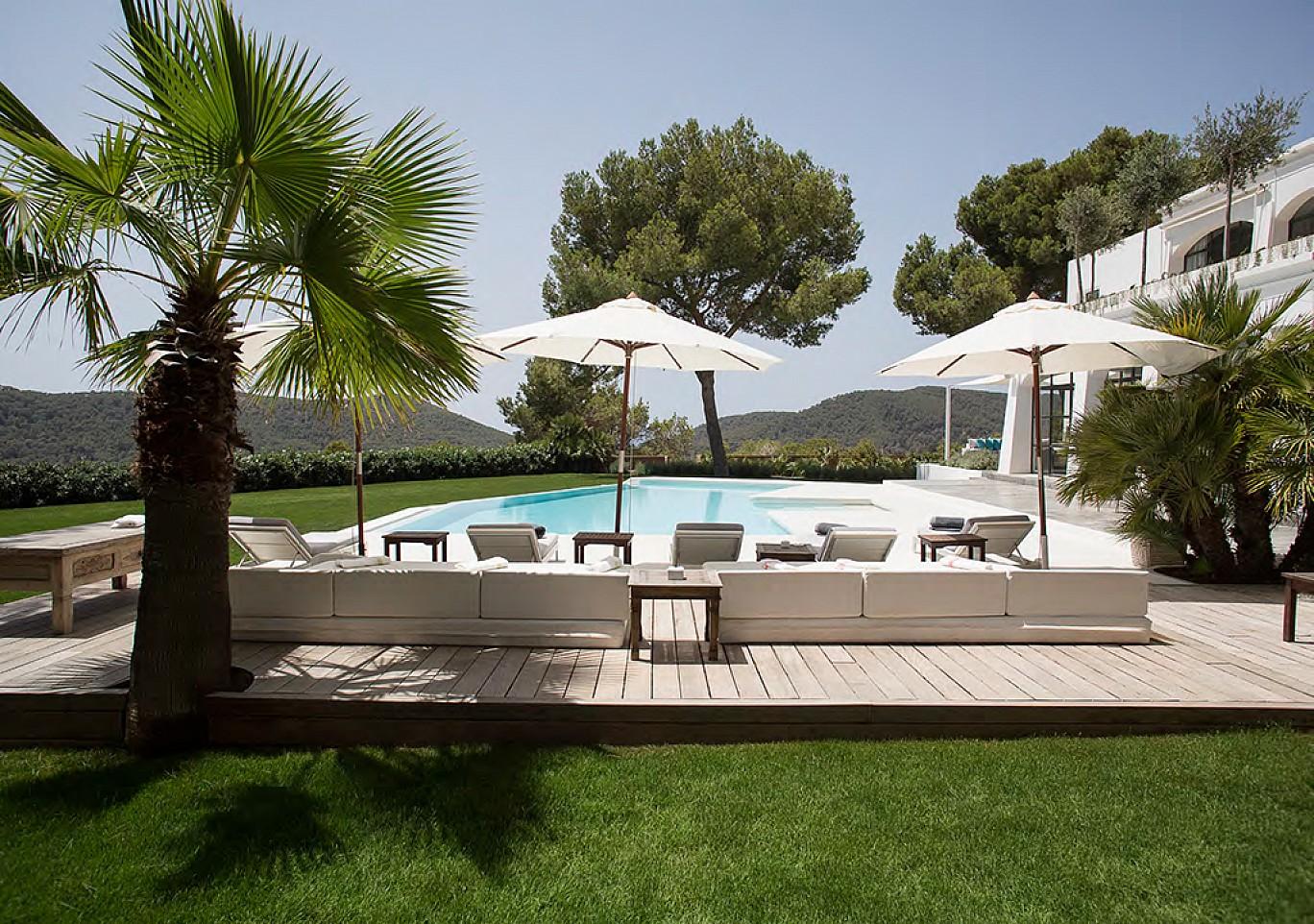 Vistas exteriores de la piscina con hamacas