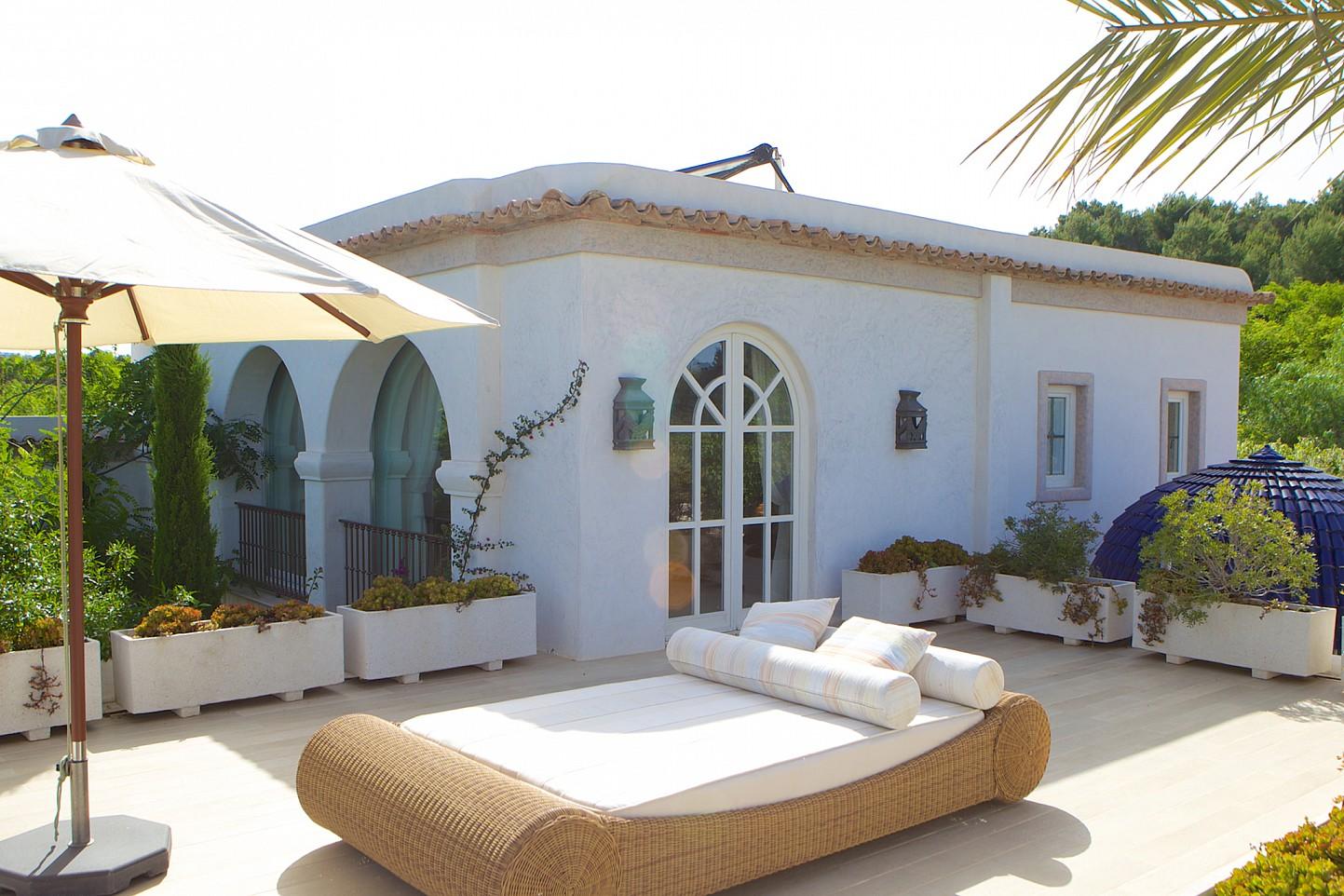 Vista d'una terrassa soleada amb un llit exterior