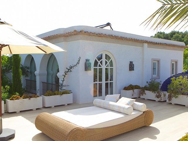Vista de una terraza soleada con cama exterior