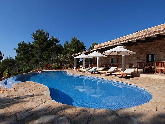 Gran piscina amb hamaques i para-sols