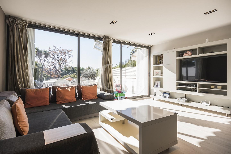 Salón-comedor soleado con grandes ventanales que conectan con el exterior