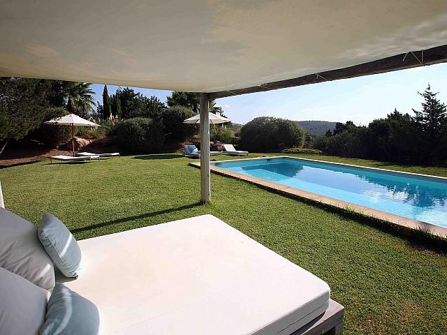 Llit extrerior al jardí amb la piscina