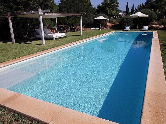 Gran piscina rodeada de hamacas