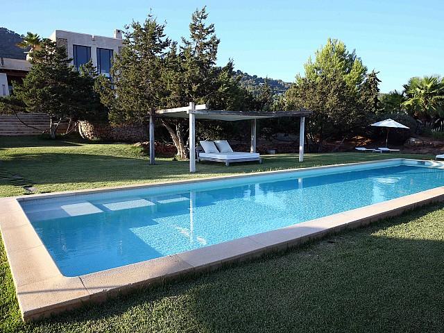 Fantástica piscina con una cama exterior