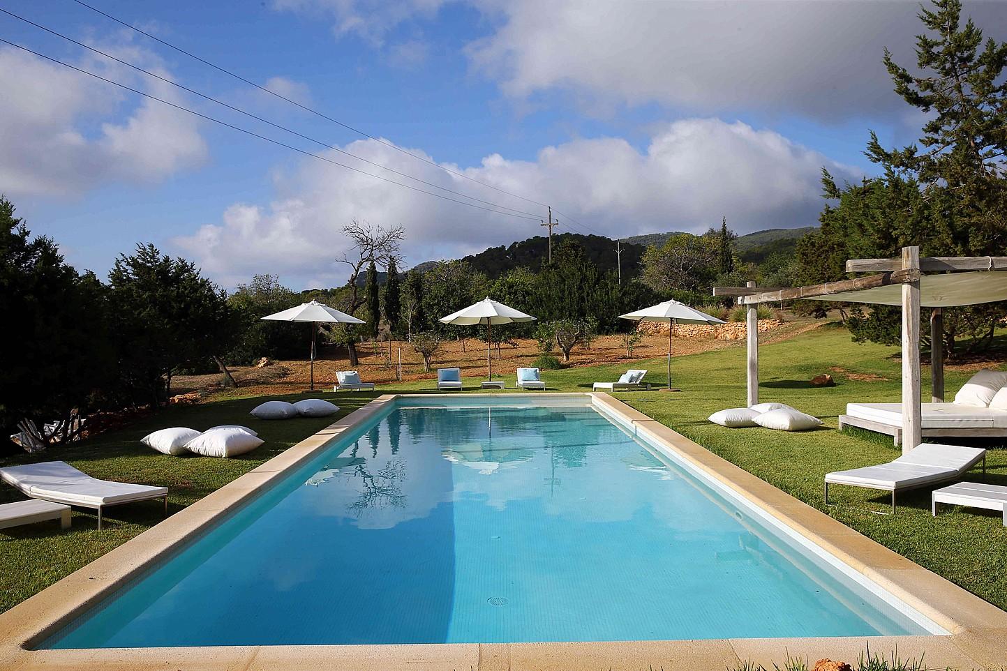 Majestuosa piscina en el jardín rodeada de hamacas