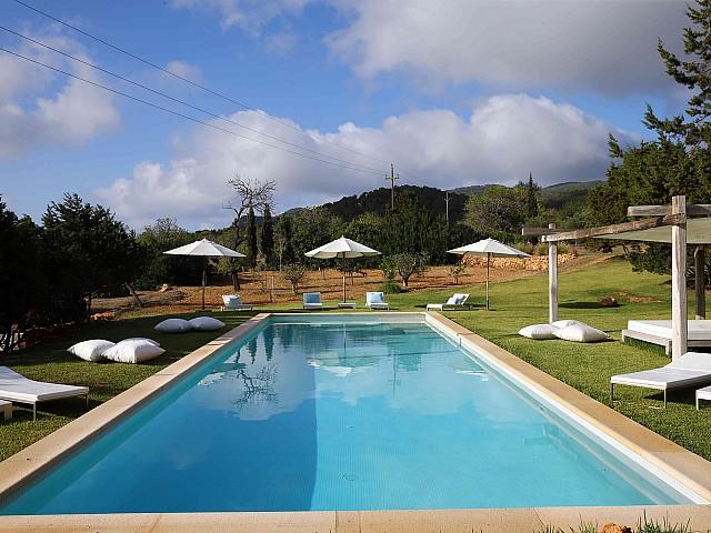 Majestuosa piscina rodejada per les hamaques