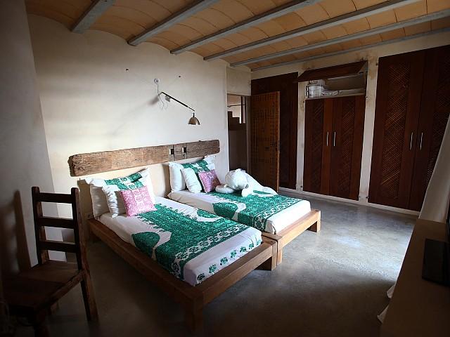 Dormitorio doble con vigas de madera en los techos