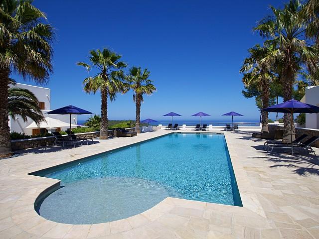Gran piscina rodeada de hamacas y palmeras