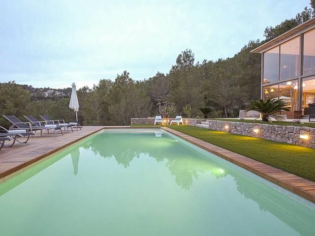 Gran piscina con hamacas en la zona del jardín